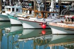 Fisherman's Wharf. Fishing boats reflecting in the waters along docks and crab restaurants of Fisherman's Wharf on San Francisco's Embarcadero. Fisherman's Wharf Stock Photo