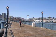Fisherman's Wharf San Fran. Lone figure walking on pier headed toward San Francisco skyline Royalty Free Stock Image