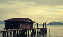 Fisherman's wooden house by the beach. Fisherman's wooden house in a cloudy day by the seaside on wooden pillars Stock Images