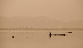 Fisherman are sailing for fishing in lake. In sepia color Royalty Free Stock Photo