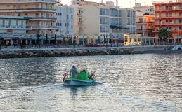 A fisherman is sailing in his boat for fish in Loutraki. Beautiful view of a fisherman sailing in his boat in Loutraki  Greece resort on Ionian sea at warm sunny Royalty Free Stock Photos