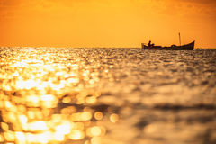Fisherman sailling with his boat on beautiful sunrise over the s Royalty Free Stock Images