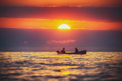 Fisherman sailling with his boat on beautiful sunrise over the s. Ea Royalty Free Stock Images
