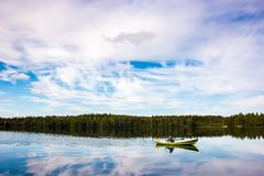 Fisherman sails on a green boat on the lake Royalty Free Stock Image