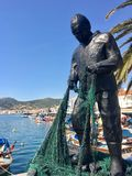 Fisherman sculptures at the middle of old Foca Harbor Izmir. The town inherited its namePhokaia b. FOÇA, TURKEY - APRIL 29, 2017: Fisherman sculptures at the royalty free stock photo