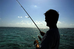 Fisherman and sea. Silhouetted fisherman with rod, sea in background Stock Image