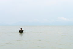 Fisherman in the sea corrects fishing net Royalty Free Stock Photography