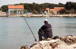 Fisherman at sea fishing Stock Photos