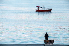 Fisherman by the sea and fishing boat in the waters of sea Stock Photos