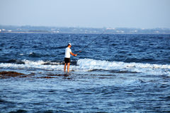 Fisherman in the sea Royalty Free Stock Image