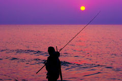 Fisherman by the sea at sunset Royalty Free Stock Photo