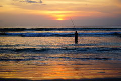 Fisherman in the sea at sunset. Stock Photos