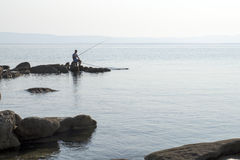 Fisherman on the seashore Royalty Free Stock Photo