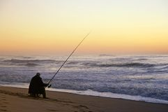 Fisherman seated. In the beach Stock Images