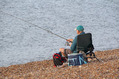 Fisherman seated with rod Royalty Free Stock Photos