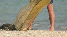 Fisherman with a seine on the beach. stock video footage