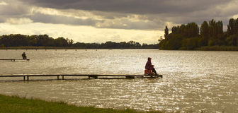 Fisherman on the shore. A fisherman is fishing from bridges Royalty Free Stock Photos
