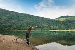 Fishing adventures, carp fishing. Angler is casting the bait. Fisherman on the shore of a lake, with camouflage t-shirt and a fishing rod in his hand, is casting royalty free stock image