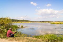Fisherman on the shore of the lake. stock images