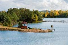 A fisherman on the shore of a small lake. Autumn landscape. A fisherman on the shore of a small lake is fishing in sunny autumn day Royalty Free Stock Images