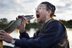 Fisherman shouting at fish. Fisherman shouting at caught pike fish Stock Photo
