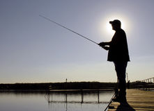 Fisherman Silhouette. A man fishes off a dock at a lake Stock Image