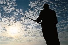 Fisherman silhouette. On cloudy sky stock image