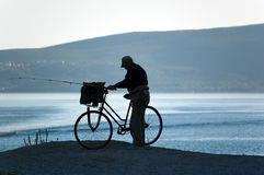 Fisherman silhouette. With the bike. Sea bay and hills in the background, summertime Royalty Free Stock Photos