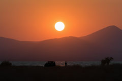 Fisherman silhouette against a beautiful sunset and the mountains as background. Royalty Free Stock Image