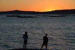 Fisherman silhouette against the setting sun Stock Photo