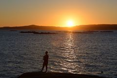 Fisherman silhouette against the setting sun Stock Photography