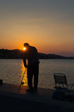 Fisherman silhouette against the sunset. Stock Image