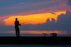 Fisherman silhouette on the beach at colorful sunset Stock Photography