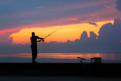 Fisherman silhouette on the beach at colorful sunset Stock Photos