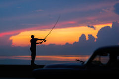 Fisherman silhouette on the beach at colorful sunset Royalty Free Stock Photo