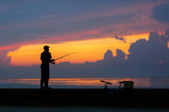 Fisherman silhouette on the beach at colorful sunset Royalty Free Stock Image