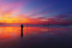 Fisherman silhouette on beach at sunset Stock Photography