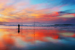 Fisherman silhouette on beach at sunset Stock Image