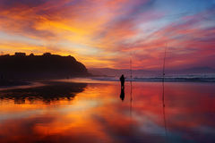 Fisherman silhouette on beach at sunset Royalty Free Stock Photography