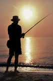 Fisherman silhouette on the beach at sunset Stock Photos