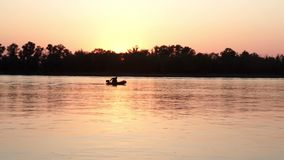 Fisherman silhouette on boat catching fish in river on background evening sunset. Landscape evening sunset fisher man sailing on river stock video