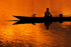 Fisherman silhouette  in Boat and River Sunset Royalty Free Stock Image