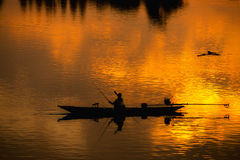 Fisherman silhouette  in Boat and River Sunset Royalty Free Stock Photos