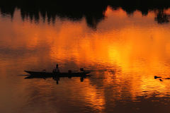 Fisherman silhouette  in Boat and River Sunset Stock Photo