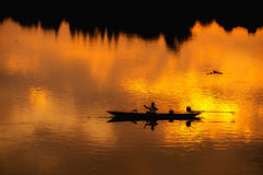 Fisherman silhouette  in Boat and River Sunset Stock Image