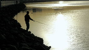Fisherman silhouette at city sunset stock video footage