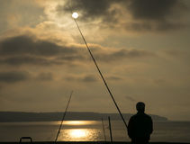 Fisherman silhouette at dusk Stock Images