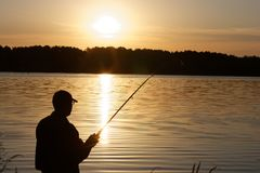 Fisherman. Silhouette of fisherman catching the fish during sunrise Royalty Free Stock Image
