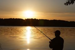 Fisherman. Silhouette of fisherman catching the fish during sunrise Stock Photography