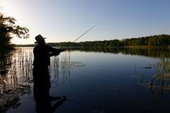 Fisherman. Silhouette of fisherman standing in the lake and catching the fish at sunny day stock images